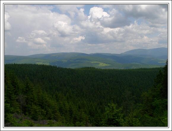 Králický Sněžník. Pohled na Rychlebské hory (Smrk). Vpravo Hrubý Jeseník (Šerák a Keprník)
