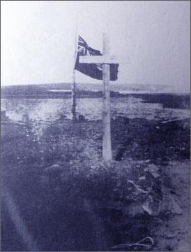 Kanadská vlajka stažená na půl žerdi u hrobu G. Mallocha a Bjarne Mamena v Rodgerově přístavu
