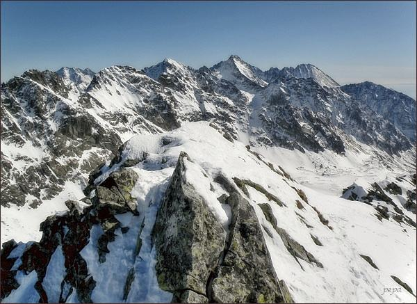 Z pohledů bočních, vzdálenějších, se Volovec mengusovský jeví jako nevýrazný vrchol. Pohled z Kôprovského štítu.  (Volovec mengusovský na druhém horizontu, vpravo )