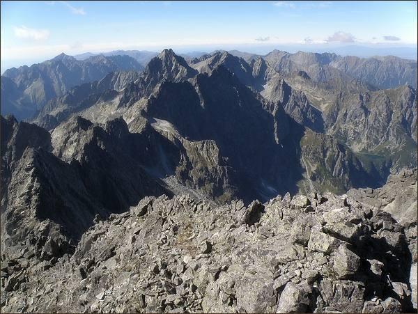 Pohled ze Zadného Gerlachovského štítu k západu. Uprostřed Koruna Vysokej, vpravo od ní Rysy. Vlevo v pozadí Kriváň. V popředí, nad Kačacou dolinou (od středu snímku) Ganek, Rumanov štít, Zlobivá, Západný Železný štít, Snehové veže, Východný Železný štít a Popradský Ľadový štít. Před ním Kačací štít a nejblíže Batizovský štít