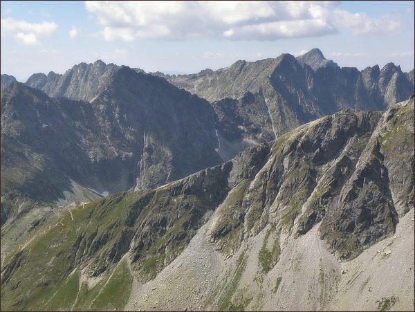 Vyšné Kôprovské sedlo z Prostredného Mengusovského štítu. Za ním vlevo Hlinská veža, Vpravo od ní Štrbský štít, Štrbské sedlo, Hrubý vrch, za ním Kriváň