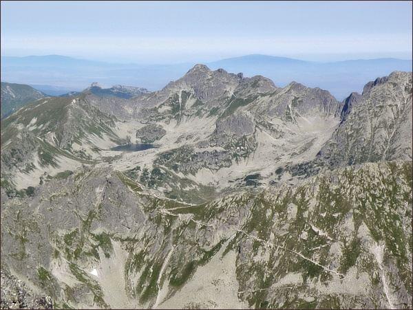 Pohled z Veľkého Mengusovského štítu k severu. V popředí vlevo Hrubý štít a sedlo Szpiglasowa Przełęcz.. Na zadním horizontu Świnica