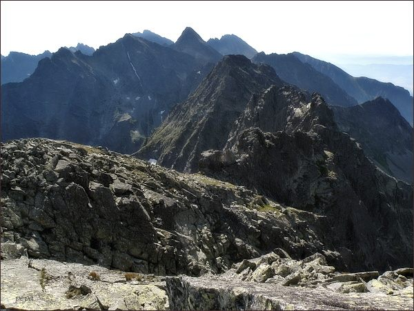 Pohled z Veľkého Mengusovského štítu k jihovýchodu. V popředí Prostredný a Východný Mengusovský štít. Na prostředním horizontu zleva Malé Rysy, Rysy a Vysoká. Na zadním horizontu Gerlachovský štít a Končistá