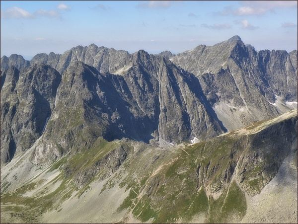 Vých. Mengusovský štít: Pohled ke Kôprovskému sedlu. Za ním zleva Capie veže, Hlinská veža, Štrbský štít. Na zadním horizontu zleva Soliskový hrebeň, Furkotský štít, Hrubý vrch, za ním Kriváň