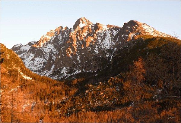 Sluneční paprsky mění šedou žulu tatranských skal v oranžově žhnoucí masu
