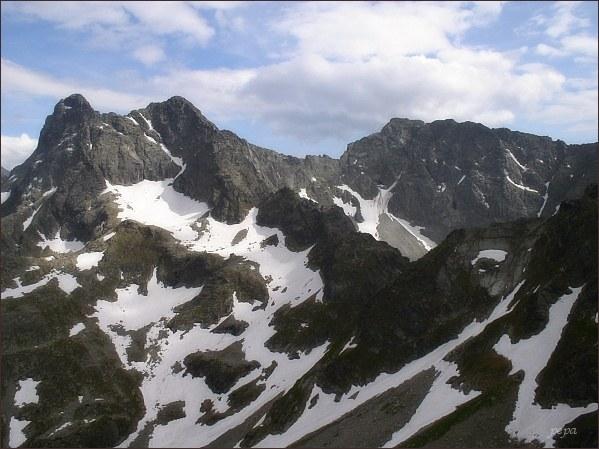 Čubrina (vpravo) ze sedla Szpiglasowa Przełęcz. Vlevo Veľký Mengusovský štít. Pod oběma vrcholy zasněžená Zadnia Galeria Cubryńska. Vpravo Kôprovský štít