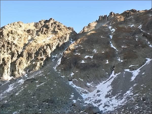 Hlinská veža (vlevo) nad Mlynickou dolinou. Uprostřed Baštové sedlo, vpravo Veľká Capia veža