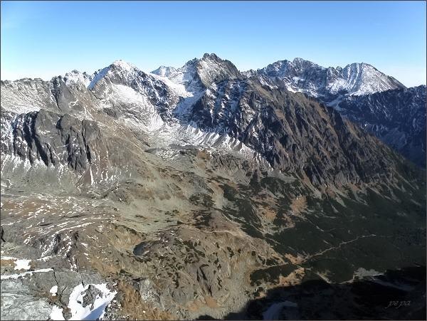 Zadná Bašta, pohled do Mengusovskej doliny. Vlevo (blíže) Mengusovský Volovec, první horizont Rysy a Koruna Vysokej, vpravo Gerlachovský štít a Končistá. Vpravo v popředí Kôpky