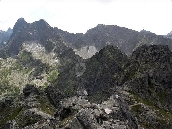Pohled z Hrubého štítu k jihovýchodu. Vlevo Veľký Mengusovský štít a Čubrina.  Vpravo Kôprovský štít.  Uprostřed vpravo Malý Hrubý štít, vlevo od něj Deravá veža a Piargová veža