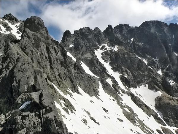 Zadná Mačacia veža (vlevo) nad Mačacím kotlom.<br /> Dále vpravo Rázsocha Lomnického štítu:<br>Ovčiarska veža, Veterný štít, Supia a Strapatá veža, Pyšné štíty