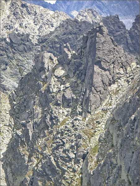 Veľká Furkotská veža od Krátkej. V levé stěně hlavního vrcholu odštípnutý balvan, kolem kterého vede výstupová cesta