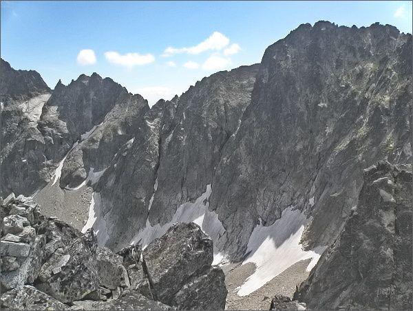 Ovčiarska veža (plochý vrchol zcela vlevo) z Čierneho štítu. Vpravo Vyšná Barania strážnica a dvojvrchol Baraních rohov